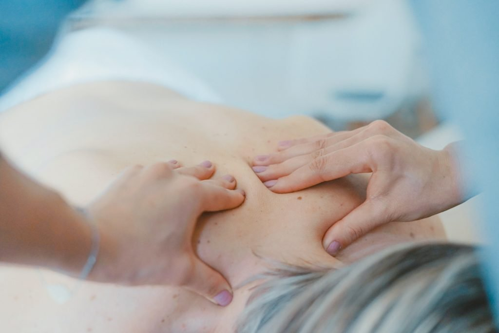 Chiropractor massaging woman's upper back