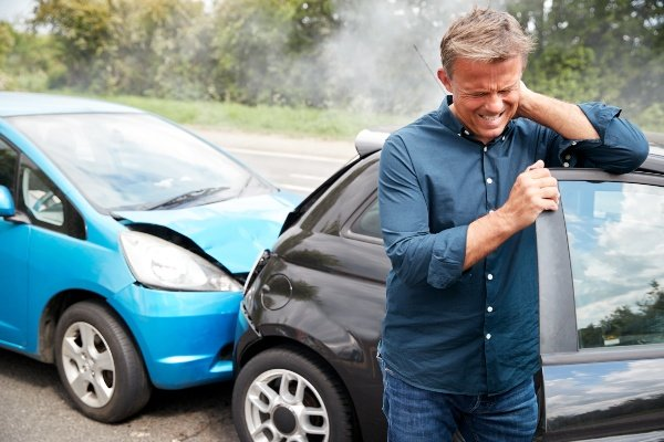 man holding his neck from pain next to car wreck
